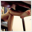 Pretty bare feet in leather pumps. Under office desk shoplay.