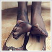 Slender nylon feet dipping worn leather flats